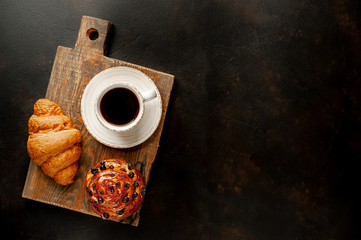 Coffee and croissant, bun on a stone table. morning breakfast, with copy space for text