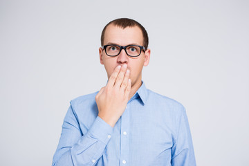 surprised or scared young businessman covering mouth with hand over gray background