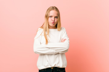 Young blonde teenager woman blows cheeks, has tired expression. Facial expression concept.