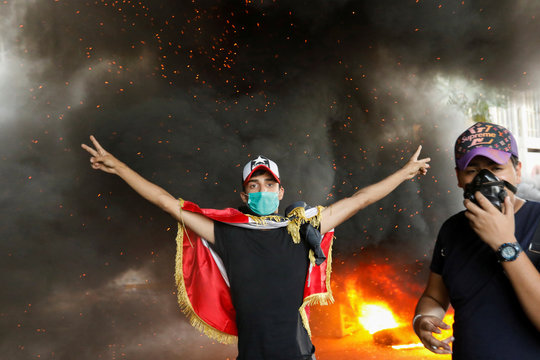 A demonstrator shows the victory signs amid a cloud of smoke during ongoing anti-government protests in Baghdad