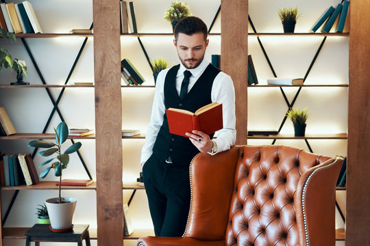 Handsome young man in elegant suit reading a book in modern luxury interior