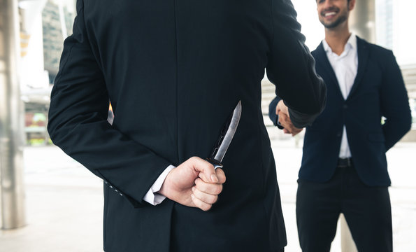 two business making handshake a deal but hiding knives