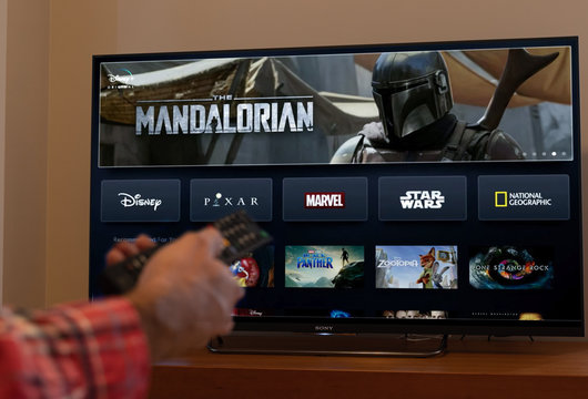 Barcelona, Spain. November 2019: Man holds a remote control With the new Disney plus screen on TV