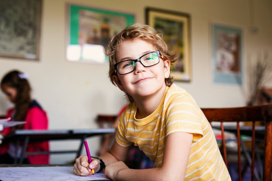Blonde boy with glasses drawing. Group of elementary school pupils in classroom on art class. Russia, Krasnodar, May, 23, 2019