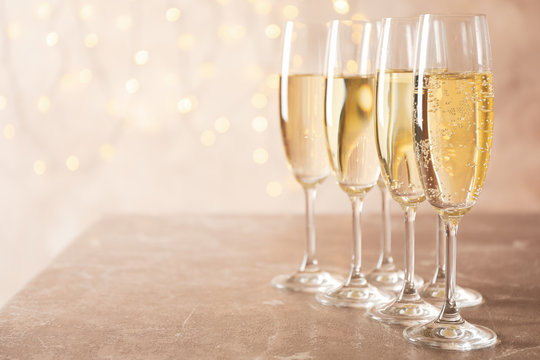 Champagne glasses against blurred lights background, space for text