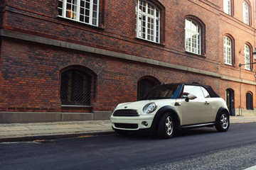 Copenhagen / Denmark - 07.24.19: Mini Cooper Cabrio Coupe parked in old street on background red brick building