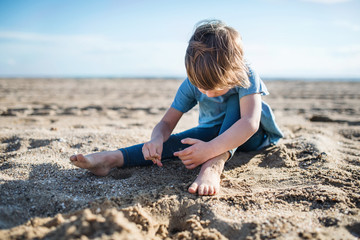 A small girl playing in sand outdoors on beach.