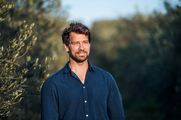 Portrait of mature man standing outdoors in olive orchard. Fotomurales