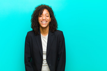 young black woman smiling positively and confidently, looking satisfied, friendly and happy against blue wall