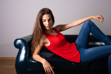 A smiling young woman lying on a sofa
