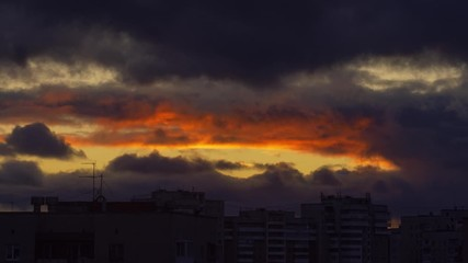 Fotobehang - Dramatic epic clouds change from red to blue as sunset sky turns into night. Timelapse, 4K UHD.