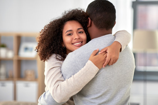 love, relationships and people concept - happy african american couple hugging at home