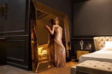 Glamorous interior golden mirror. Fashion Beautiful young woman