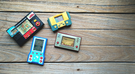Old portable game console, Nintendo game & watch octopus and others on wooden background.