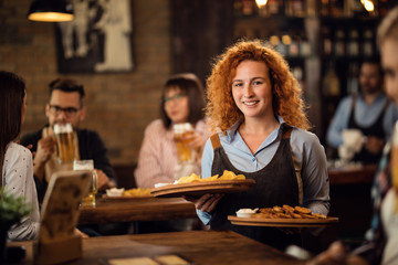 Young happy waitress serving her guest in a pub.