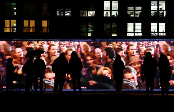 People stand in front of a projection on the East Side Gallery, the largest remaining part of the former Berlin Wall, in Berlin