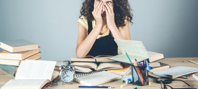 sad girl hand in face with books on desk