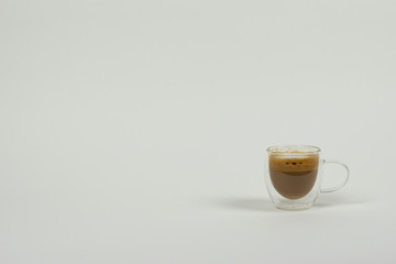 Coffee with milk in modern cup on white background