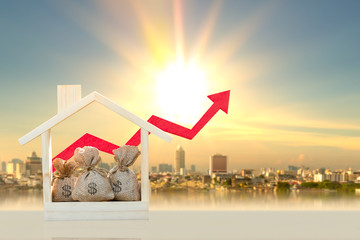 Money bags in the wooden home model and red arrow graph with growing value on photo blur cityscape background, Loan and business investment for real estate concept.