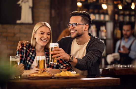 Cheerful couple toasting with beer and having fun in a pub.