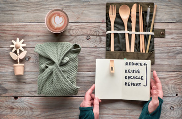 """Flat lay, zero waste lunch concept - set of reusable wooden cutlery, lunch box in textile, coffee in reusable coffee cup. Sustainable lifestyle, hands holding text """"reduce, reuse, recycle, repeat""""."""