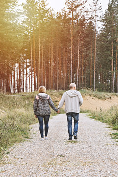 Middle-aged couple of baby boomers people walking in forest