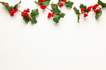 Christmas background with branches of holly with red berries on white. Winter concept. Flat lay, copy space.