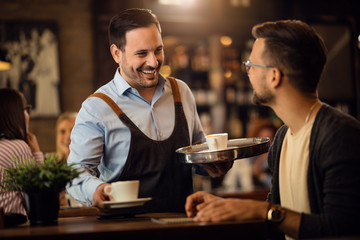 Happy waiter talking to a man while serving him coffee in a cafe.