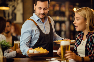 Smiling waiter serving tortilla chips to a woman in a pub.