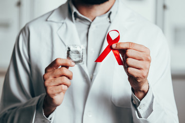 Red ribbon for HIV illness awareness in doctor's hand, 1 December World AIDS Day concept.