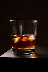 Spoed Foto op Canvas Alcohol A glass of whiskey with ice on a wooden table. Low key. Vertical orientation.