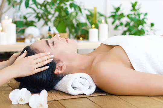 Young pleased woman is getting head massage, therapy. Female hands of master are massaging kneading temples of client. Brunette girl is lying on couch in spa ayurveda salon. Relax and health care.