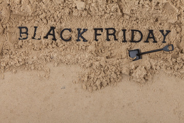 The concept of the inscription Black Friday placed in a sand hole dug with a shovel. Wall mural