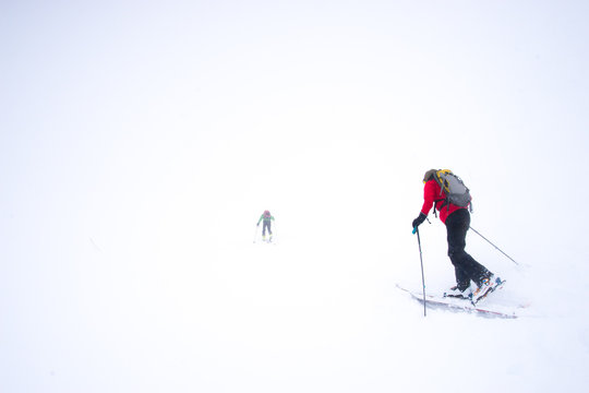 Two skiers struggling into a snow storm during a whiteout in the mountains