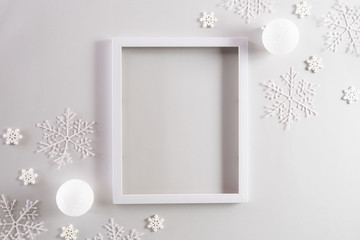 Christmas background concept. Top view of Christmas ball with picture frame and snowflakes on light gray pastel background.