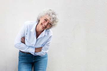 older woman laughing with arms crossed by gray wall