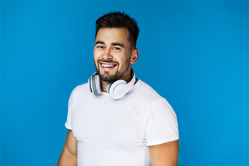 Smiling handsome man holds his headphones on the neck and looks at the camera