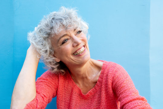 happy older woman smiling by blue wall