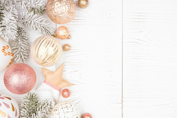 Wall Mural - Christmas side border of snowy branches and dusty rose, gold, and white ornaments. Top view on a white wood background.