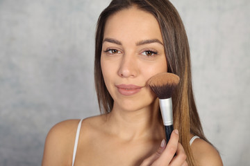 Make up and beauty concept, young woman applying powder with brush, clean skin