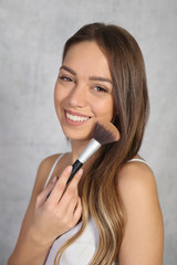 Make up and beauty concept, young woman applying powder with brush, clean skin , perfect smile