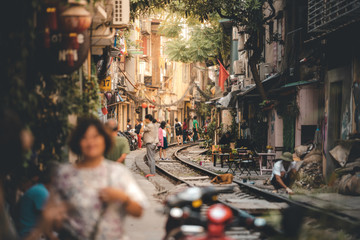 Tourists walk down and drink coffee along the tracks of the famous Train Street in Hanoi, Capital of Vietnam