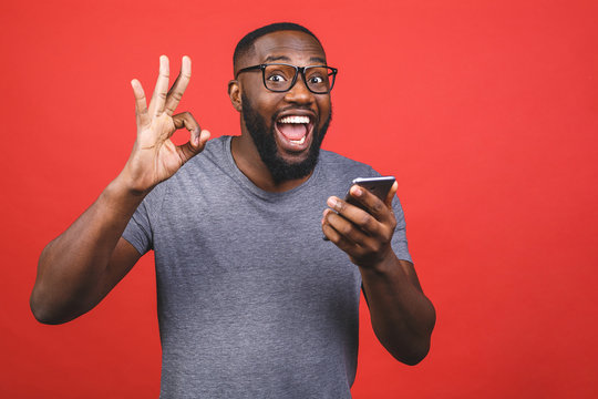 Afro american man using smartphone over isolated red background doing ok sign with fingers, excellent symbol.