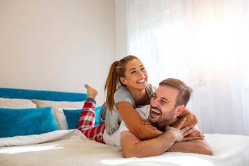Happy man and woman lying in the bedroom stock photo. Beautiful young couple in bedroom is lying on bed. Enjoying spending time together. A photo session of a guy and a girl