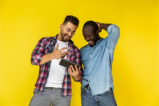 european and afroamerican guys are looking on the tablet and laughing on the yellow background