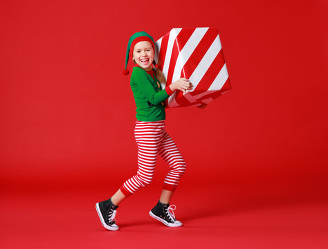cheerful funny baby in Christmas elf costume with gifts on   red background.