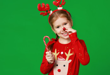 happy funny child girl in red Christmas reindeer costume with gift on green   background.