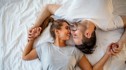 Guy and a girl in a cozy home environment. Happy man and woman lying in the bedroom stock photo. Top view of smiling young couple cuddling in bed in morning.  Beautiful pair of lovers hug and kiss