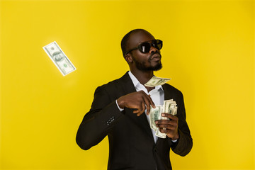 bearded solid young afroamerican guy is throwing out dollars from one hand, wearing sunglasses and black suit on the yellow background Wall mural