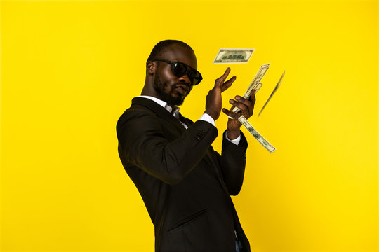 Handsome afroamerican guy scatters money and looks selfish